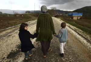 Sawssan Abdelwahab, who fled Idlib in Syria, walks with her children outside a refugee camp near the Turkish-Syrian border. (Photo: REUTERS/Zohra Bensemra)